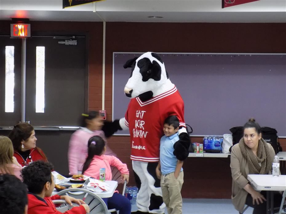 Students being photographed with chick-fil-A costume cow.